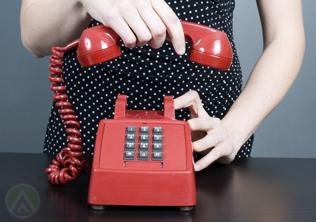 woman hanging up landline phone