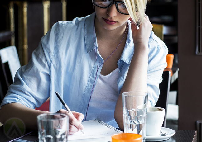 woman writing journal inside restaurant