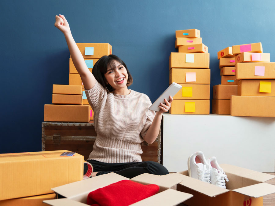 Excited woman ecommerce online shopping surrounded by boxes