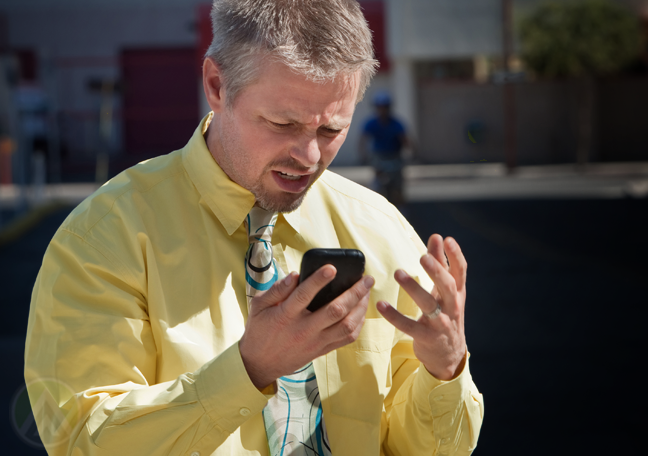 annoyed businessman in yellow shirt looking at smartphone outdoors