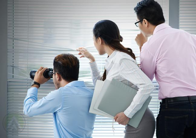 business team looking out office window using binoculars