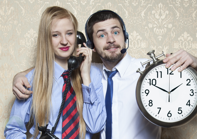 call center agent holding wall clock with customer using phone