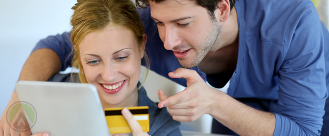 couple looking at tablet holding tablet credit card online shopping ecommerce