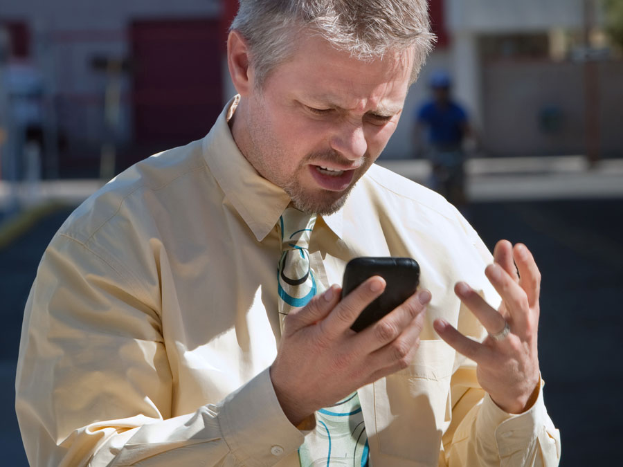 frustrated man looking at smartphone
