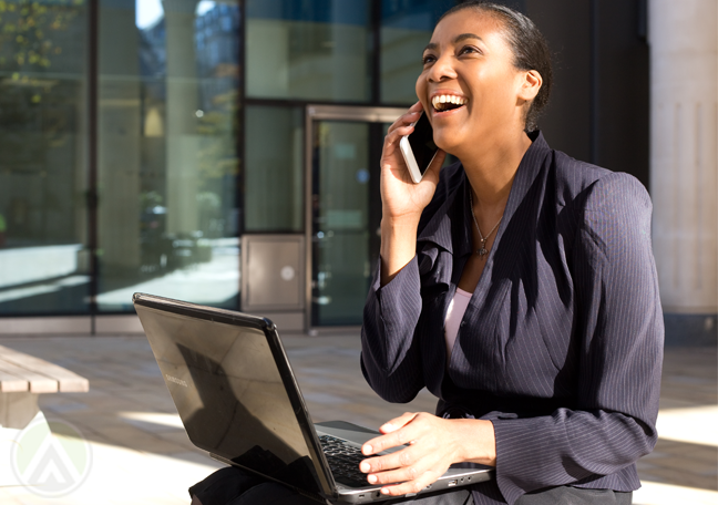 happy business woman laughing during phone call using laptop