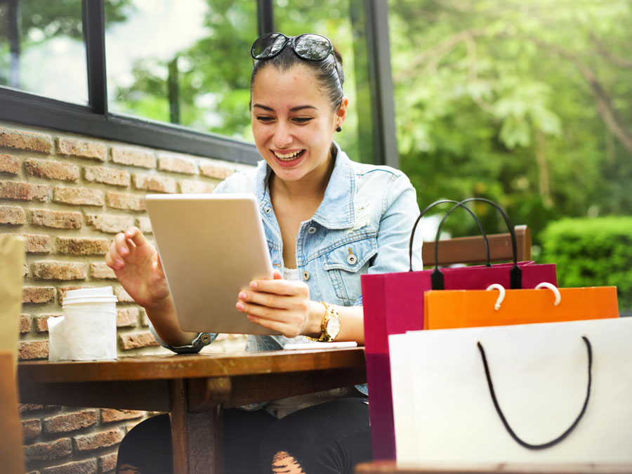 happy woman online shopping on tablet at cafe with shopping bags