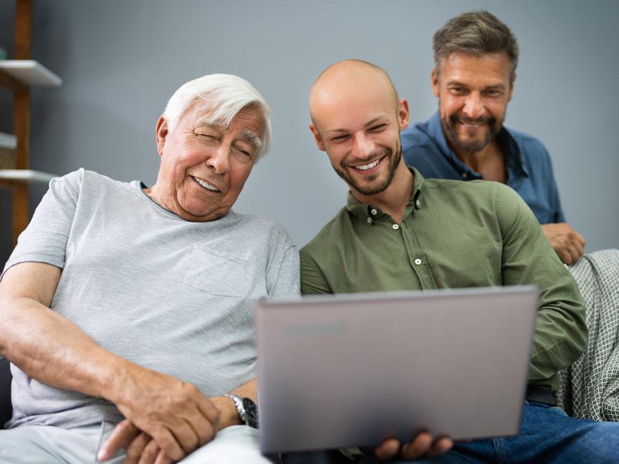 multigeneration grandfather son grandson using laptop for ecommerce online shopping