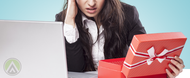 problematic female call center agent sitting by laptop looking at red opened gift box