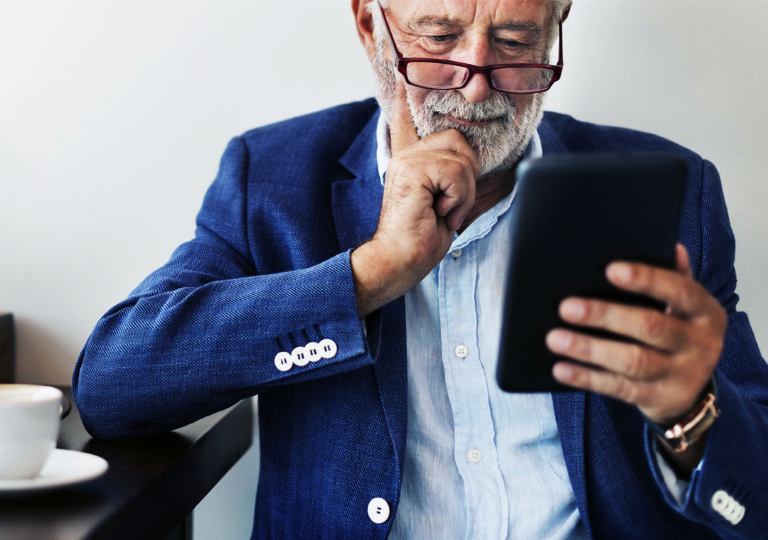senior man with customer care preferences thinking holding tablet online shopping site
