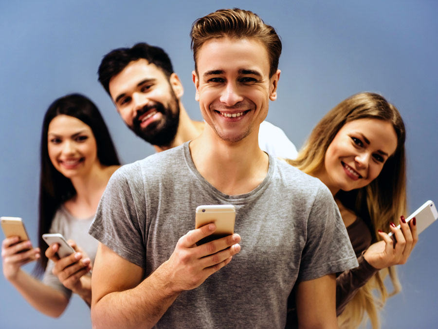 smiling group of friends holding phones