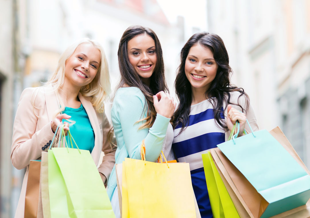 smiling ladies with customer care preferences holding online shopping bags