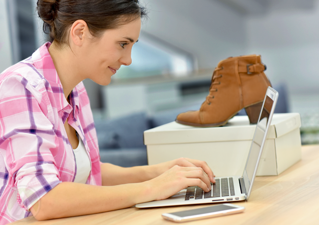 woman using laptop next to box with brown shoes