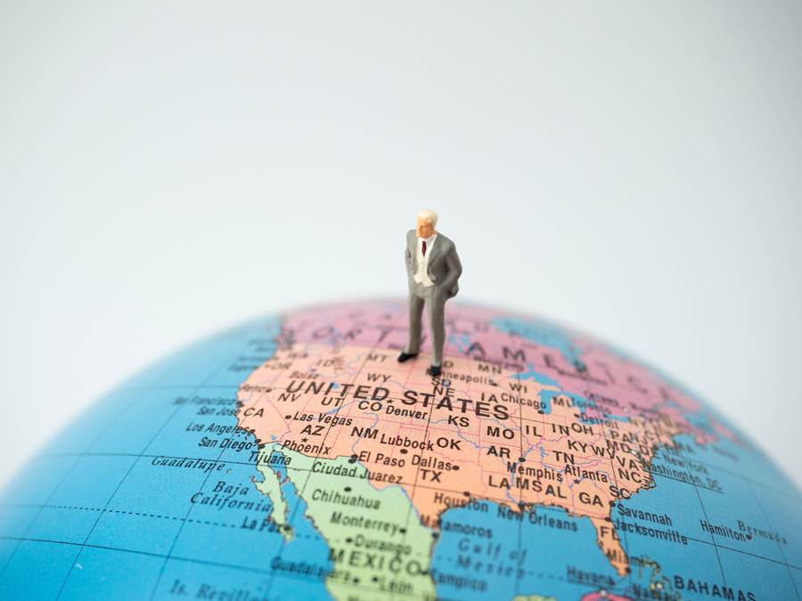 lone miniature businessman standing on top of globe