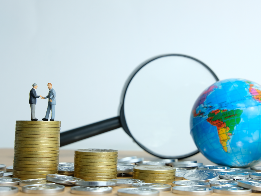 miniature business partners on stack of coins magnifying lens globe
