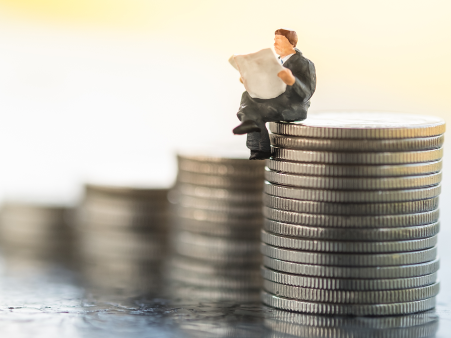 miniature executive reading newspaper on stack of coins showing business progress