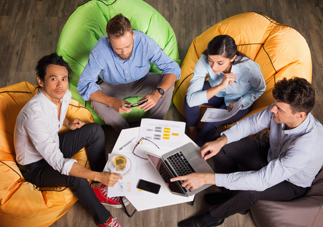 office employee working together sitting on colorful bean bag chairs showing teamwork