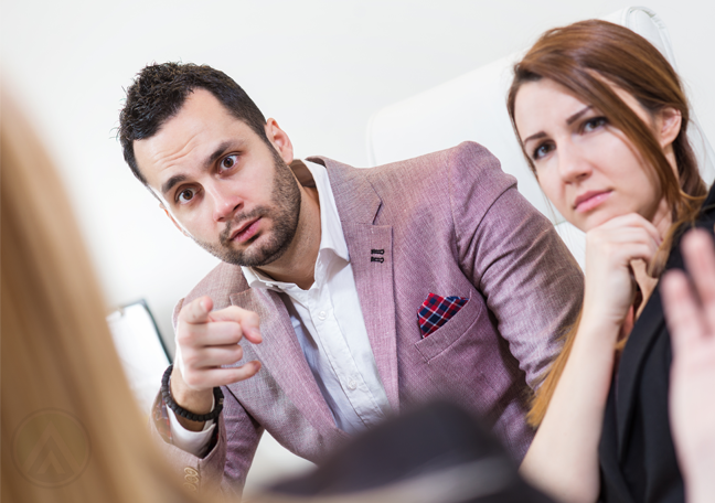 office employee pointing blame on coworker during meeting showing failed office culture