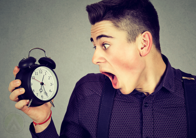 panicking young employee shocked holding alarm clock