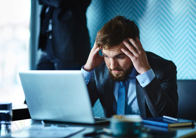 worried businessman with headache in office looking at laptop
