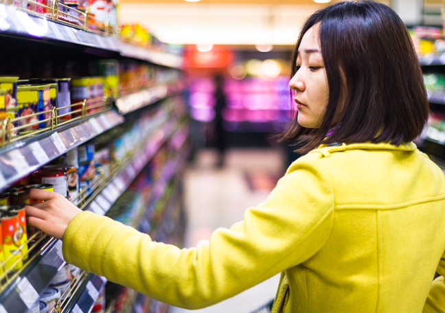 Chinese woman wearing yellow in grocery reaching for can of food