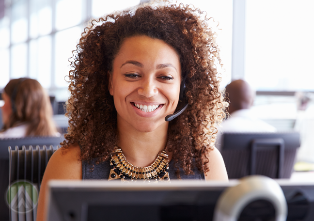 brightly smiling woman at work talking to customer over headset