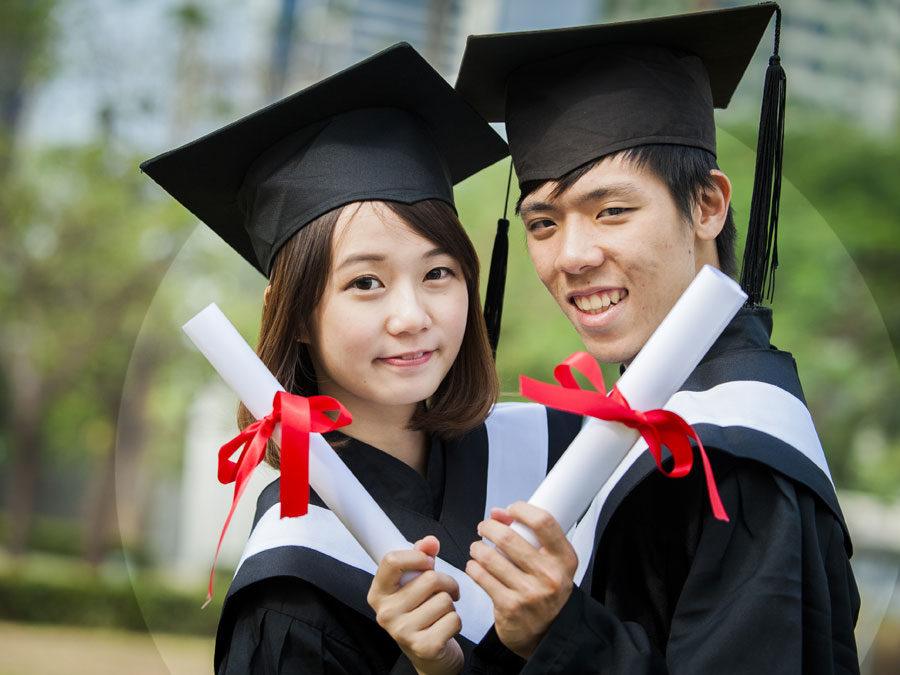chinese asian couple graduates wearing graduation gown cap