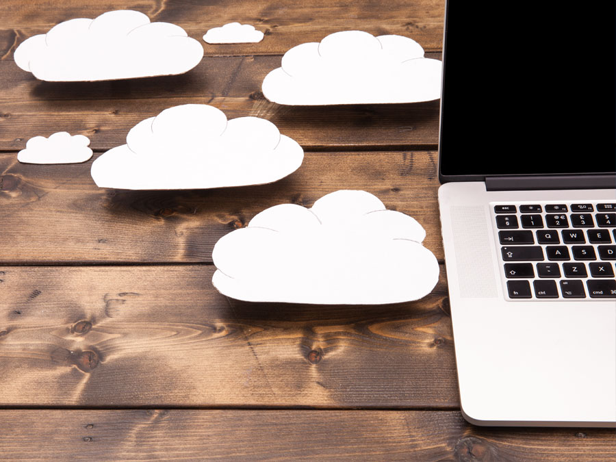 macbook laptop on table with paper cutout clouds concept cloud computing