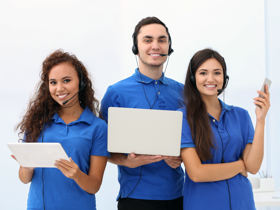 multichannel business team in blue in call center using laptop tablet smartphone