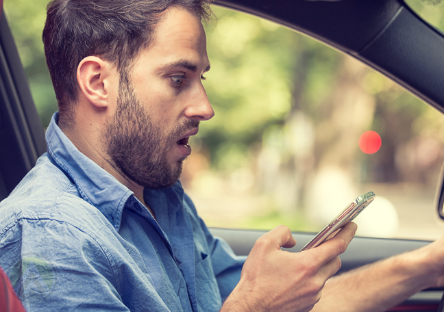 surprised man driving car looking at customer support message on smartphone