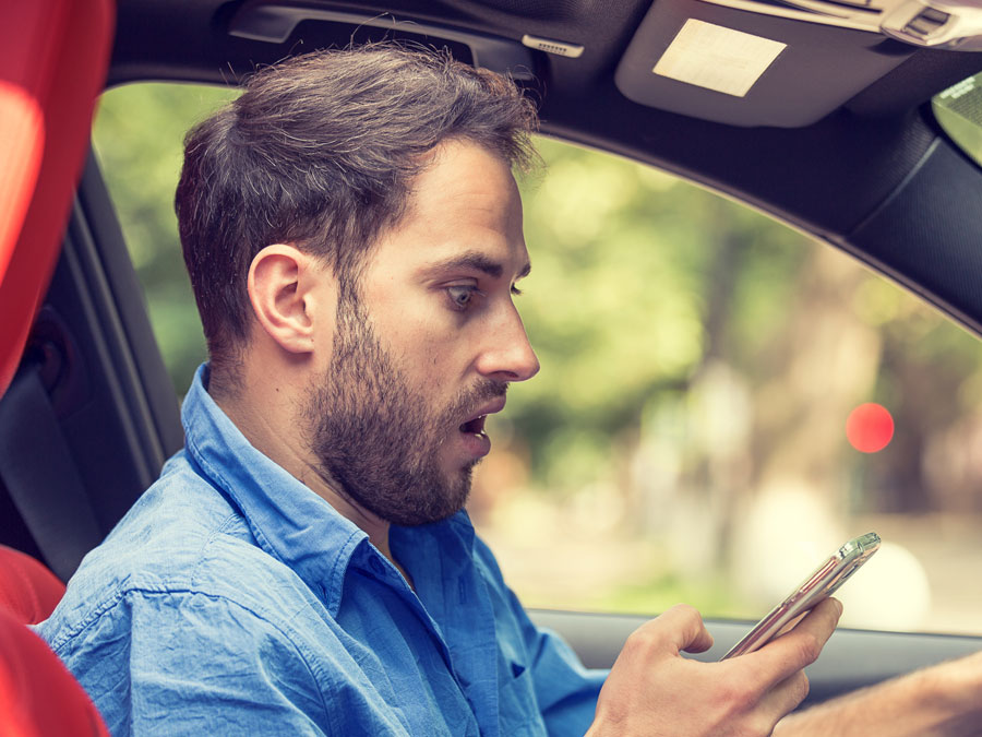 surprised man in car staring at phone