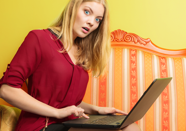 surprised-woman-sitting-on-couch-in-bright-room-using-laptop