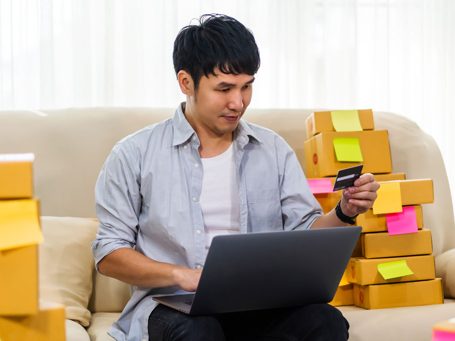 young chinese asian holding credit card doing online shopping ecommerce boxes
