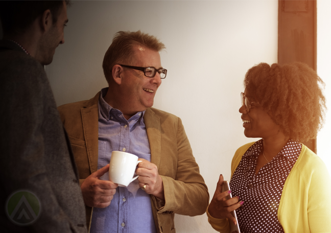 diverse coworkers chatting by hallway having coffee