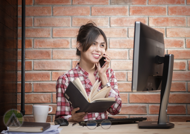 happy woman holding book by computer calling customer support hotline