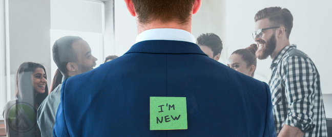 new employee in suit to his back with im new post it note