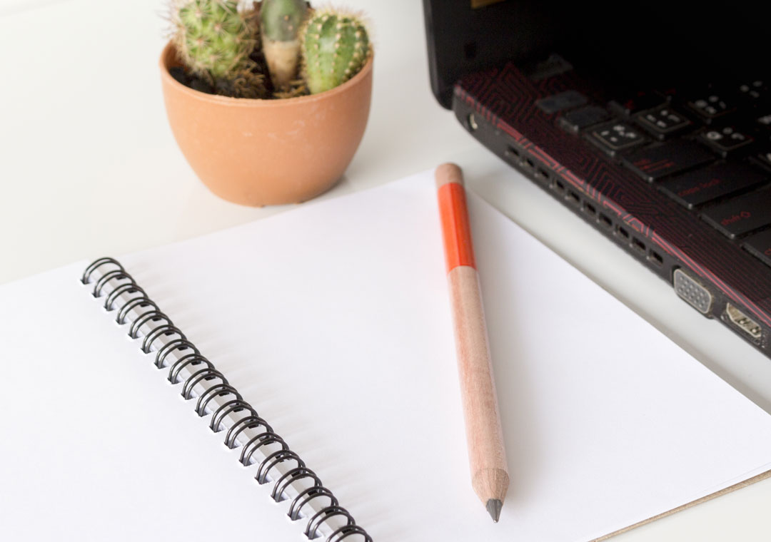 notepad pen near laptop