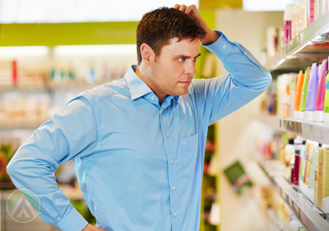 young man thinking scratching head looking at grocery items