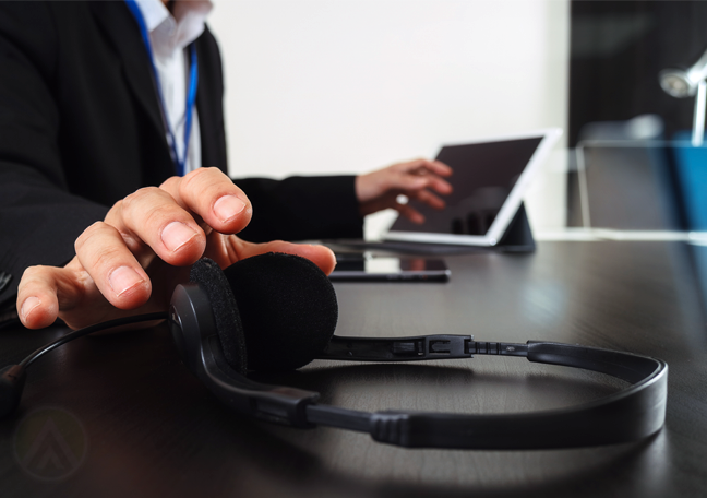 businessman reaching for tablet headset office table