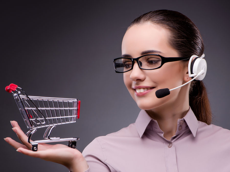 smart ecommerce call center agent holding miniature shopping cart