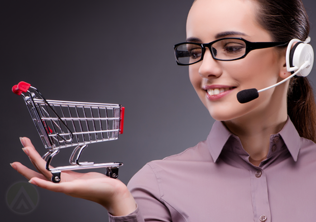 smiling customer service call center agent holding up tiny miniature shopping cart