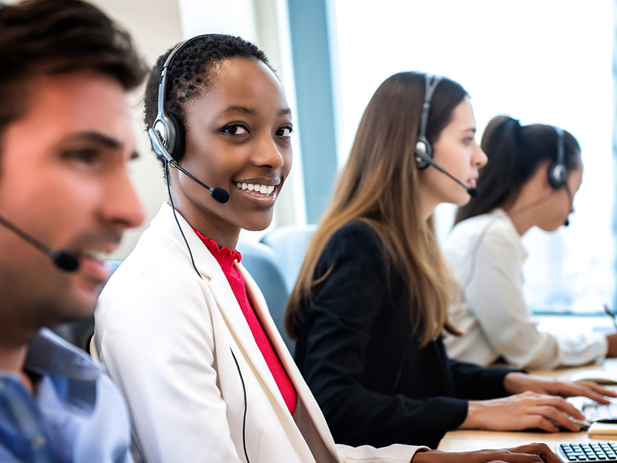 smiling customer service specialist speaking to customer in call center