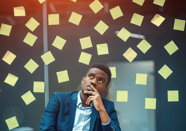 young businessman thinking deeply looking away surrounded by post it notes