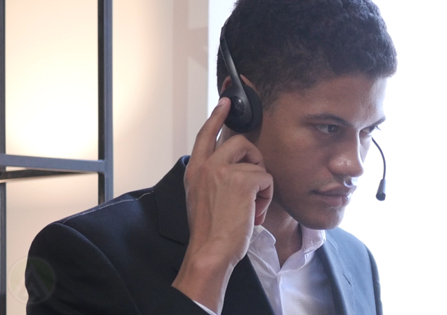 young call center agent listening intently to customer on headset