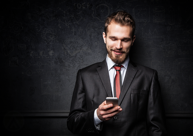 smiling businessman in dark using smartphone