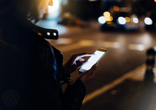 woman back using smartphone street at night