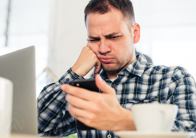 disappointed office worker staring at smartphone