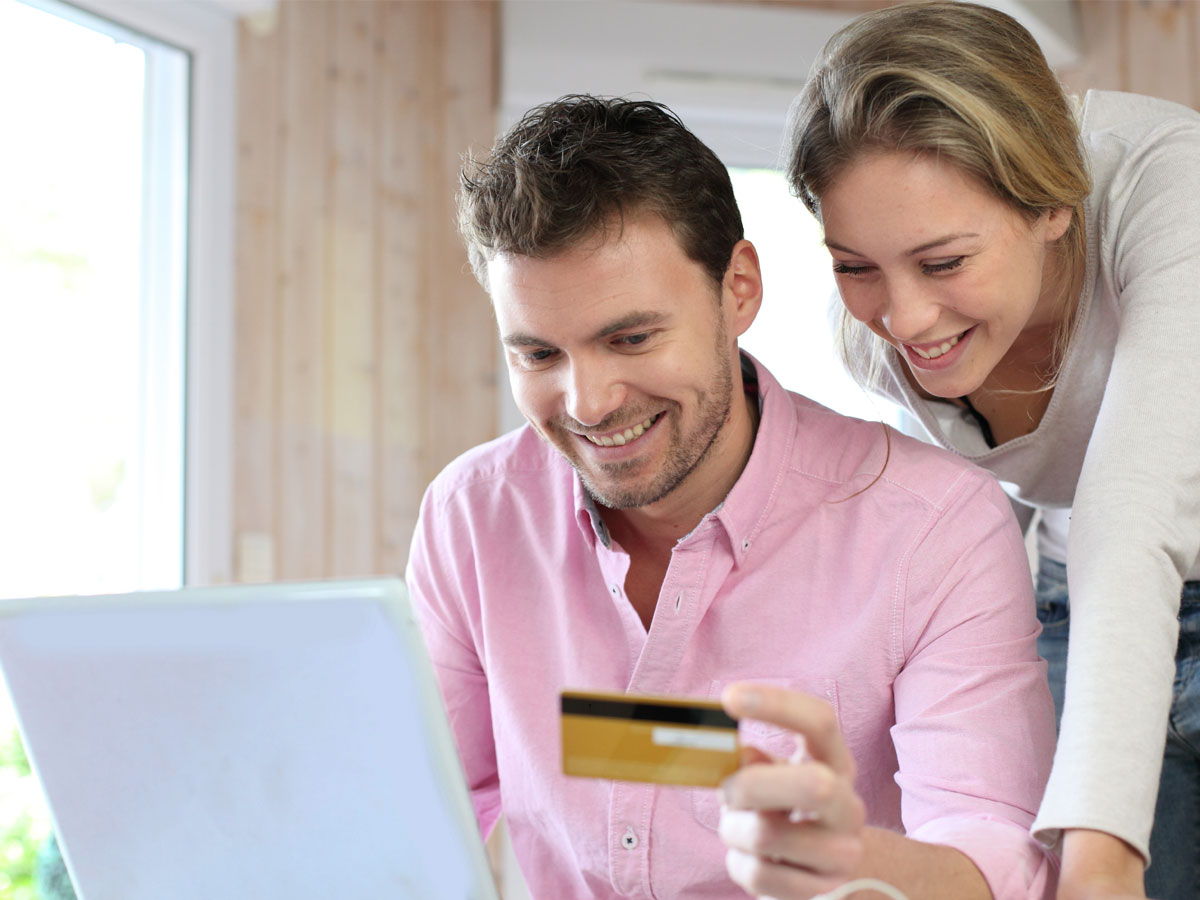 couple happily online shopping on ecommerce website using laptop
