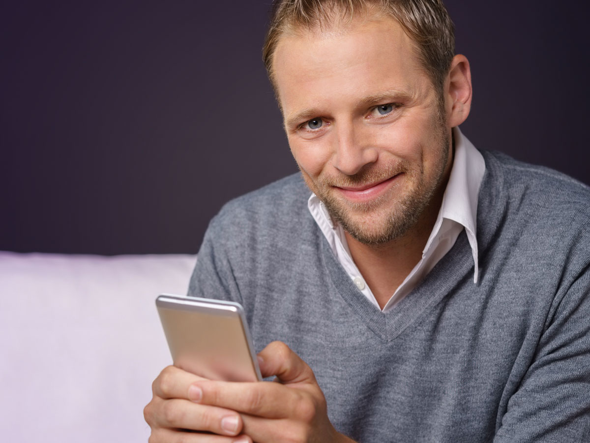 smiling man holding mobile phone