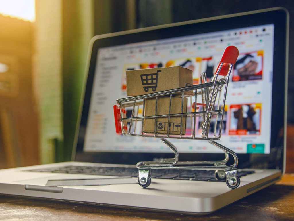 tiny shopping cart with packages on laptop on e-commerce website