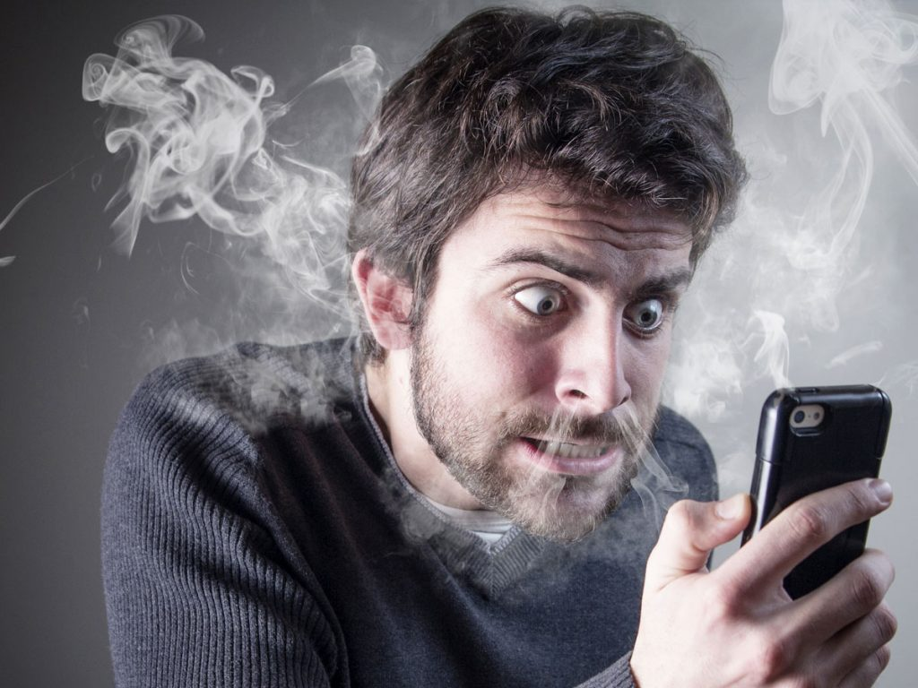 frustrated young man staring at phone as smoke blows from nose